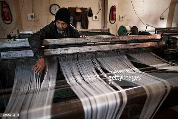 Syrian employee Mahmud checks a loom in the textile factory where he works in the Sheikh Majjar complex of Aleppo in northern Syria on January 7 2013...