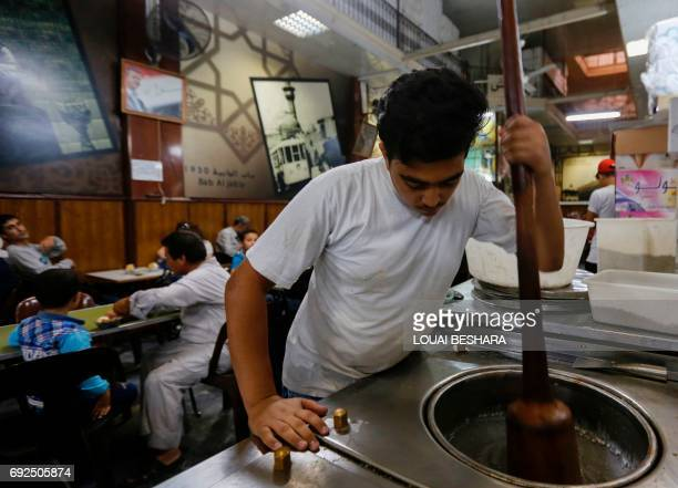 A Syrian employee makes traditional icecream at the famous 'Bagdash' sweet shop in the Hamidiyeh popular market in the old part of the capital...