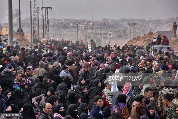 TOPSHOT Syrian families fleeing from various eastern districts of Aleppo queue to get onto governmental buses on November 29 2016 in the...