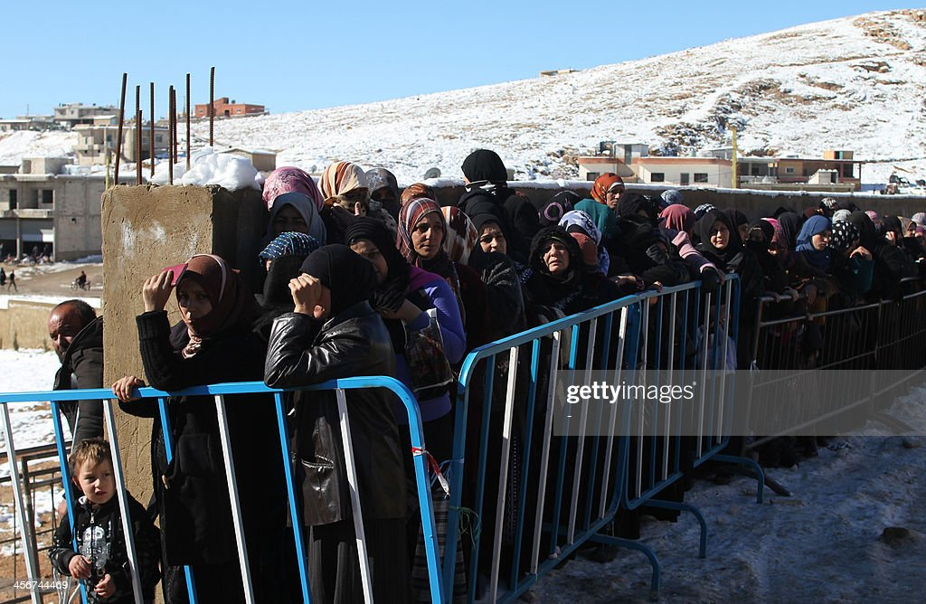 Syrian families queue in the snow to be registered by the United Nations High Commissioner for Refugees (UNHCR) on December 15, 2013 in the Arsal refugee camp in the Lebanese Bekaa valley. Thousands of Syrian refugees living in makeshift camps in Lebanon were weathered a winter storm that brought snow, rain and freezing temperatures to the country.