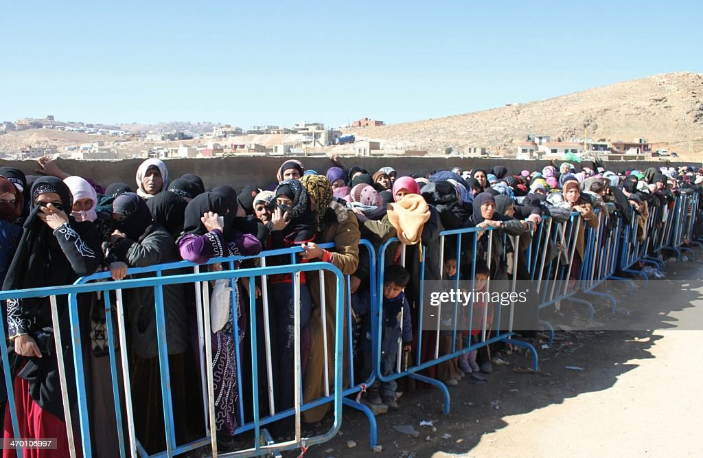 Syrian families queue to be registered by the United Nations High Commissioner for Refugees on February 18 2014 in the Arsal refugee camp in the...