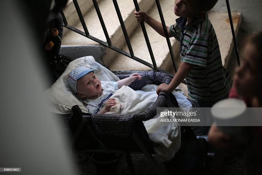 A Syrian family arrives for a medical consultation at a clinic run by a local non-profit organisation called the Union of Free Syrian Doctors, in the rebel-controlled Syrian village of Utaya, in the eastern Ghouta region on the outskirts of the capital Damascus, on May 31, 2016. The non-government organisation offers medical services in the area in the absence of public services provided the state. / AFP / ABDULMONAM