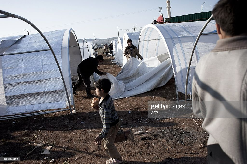 A Syrian family erects their tent at the Bab al-Salama refugee camp on the Syrian-Turkish border on January 1, 2013. Turkey, which supports the insurgency, is housing a total of some 150,000 Syrian refugees at camps near the border. AFP PHOTO / ACHILLEAS ZAVALLIS