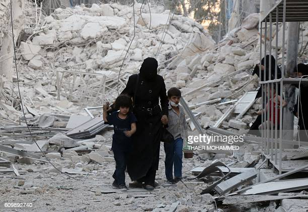 A Syrian family leaves the area following a reported airstrike on September 23 on the alMuasalat area in the northern Syrian city of Aleppo Missiles...