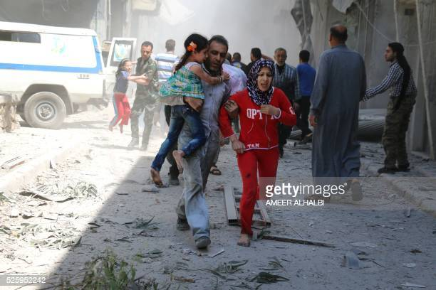 Syrian family runs for cover amid the rubble of destroyed buildings following a reported air strike on the rebelheld neighbourhood of AlQatarji in...