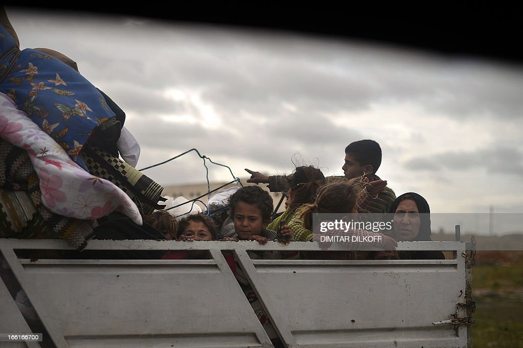 A Syrian family sit in the back of truck as they leave the northern Syrian city of Aleppo on April 9, 2013. The UN is hiking its estimates of people trapped in Syria after fleeing their homes, saying some four million are now displaced inside the country and in dire need of international help.