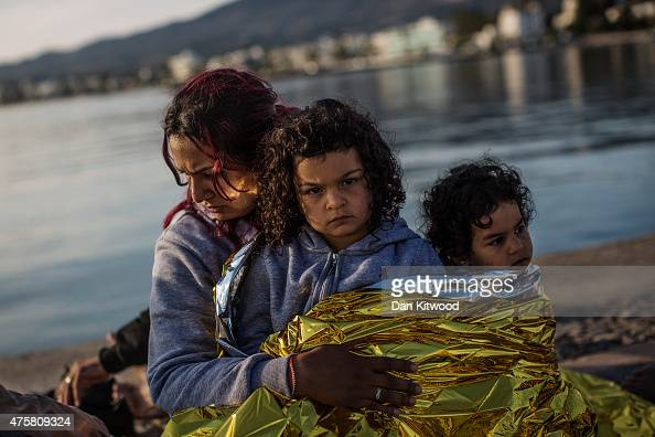 Syrian family sit on the dock side after being escorted into the harbour by the Greek Coastguard who found them drifing offshore on June 04 2015 in...