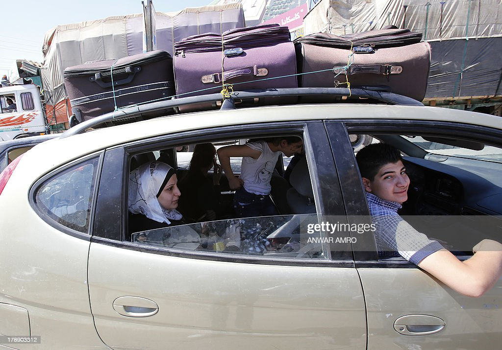 A Syrian family sits inside their car loaded with suitcases as they cross the Masnaa border post between Syria and Lebanon on August 31, 2013 in the Lebanese eastern Bekaa valley. As UN inspectors crossed the border from Syria into Lebanon, they were followed out of the war-torn country by a continuous flow of families desperate to flee the threat of US strikes. US President Barack Obama said that his administration was looking at the possibility of a 'limited, narrow act' over the suspected attack that reportedly killed hundreds, which Washington blames on the regime. AFP PHOTO/ANWAR AMRO