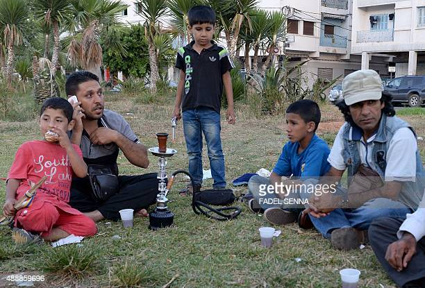 A Syrian family sits on September 17 2015 at a park where around 1000 Syrians migrants are gathering in the Moroccan town of Nador waiting to cross...