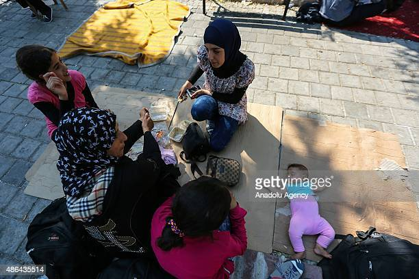 Syrian family who escaped from Syria sit at a park in Izmir Turkey on September 3 2015 Syrians who came to Turkey's Izmir province to go to European...