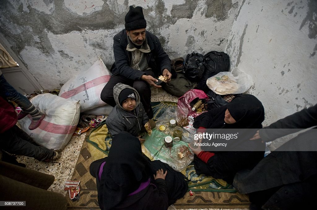 A Syrian family who fled bombing in Aleppo, eat their food after they took shelter at the courtyard of a mosque at the Oncupinar crossing, opposite the Turkish province of Kilis, near Azaz town of Aleppo, Syria on February 6, 2016. Thousands of Syrians have massed on the Syrian side of the border seeking refuge in Turkey.