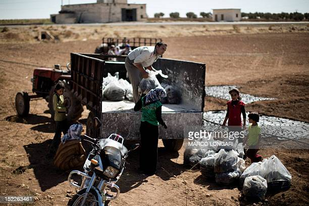 Syrian farmers load bags of dried waste of pressed olives mixed with water in a field near the battled Syrian city of alBab on September 16 2012...