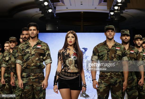 Syrian Fashion Designer Manal Ajaj walks down the catwalk with male models wearing Syrian Army uniforms at the end of her fashion show 'Jasmin...