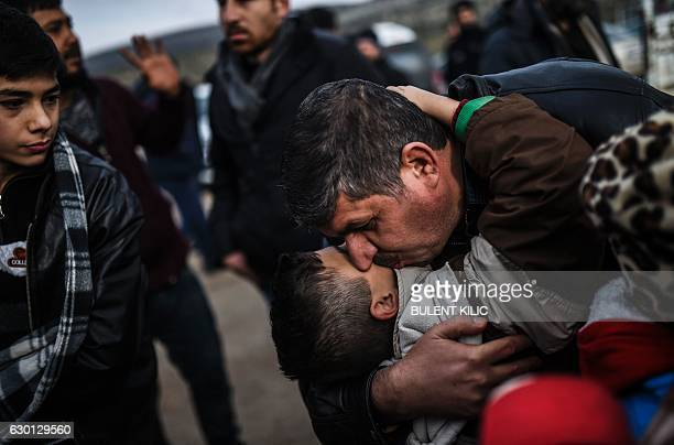 TOPSHOT Syrian father Ali embraces one of his children Zeyn upon their arrival from the Syrian city of Idlib to the Turkish crossing gate of...