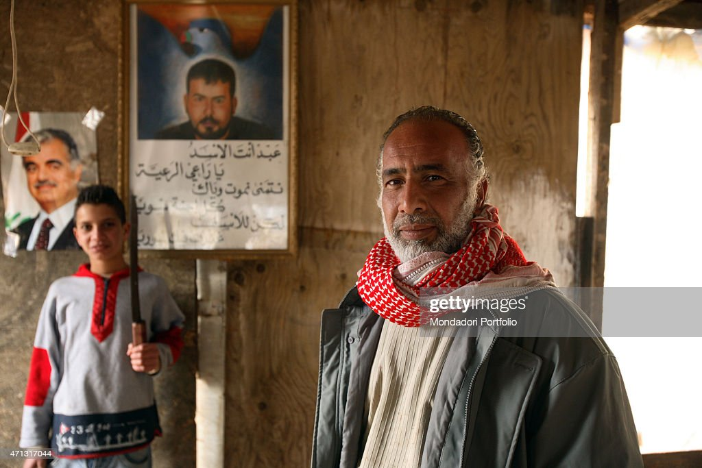 Syrian father and son posing in their poor house in the Southern district of Ramlet al-Baida, beside the images of the former premier Rafik al-Hariri and the Syrian president's son <a gi-track='captionPersonalityLinkClicked' href=/galleries/search?phrase=Basil+al-Assad&family=editorial&specificpeople=504926 ng-click='$event.stopPropagation()'>Basil al-Assad</a>. There's a building project for pulling down the hovels and leave the room for new touristic and residential buildings. Beirut, Lebanon. January 2006