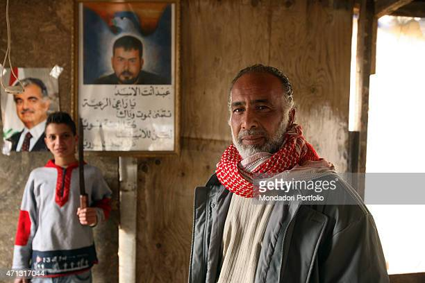 Syrian father and son posing in their poor house in the Southern district of Ramlet alBaida beside the images of the former premier Rafik alHariri...