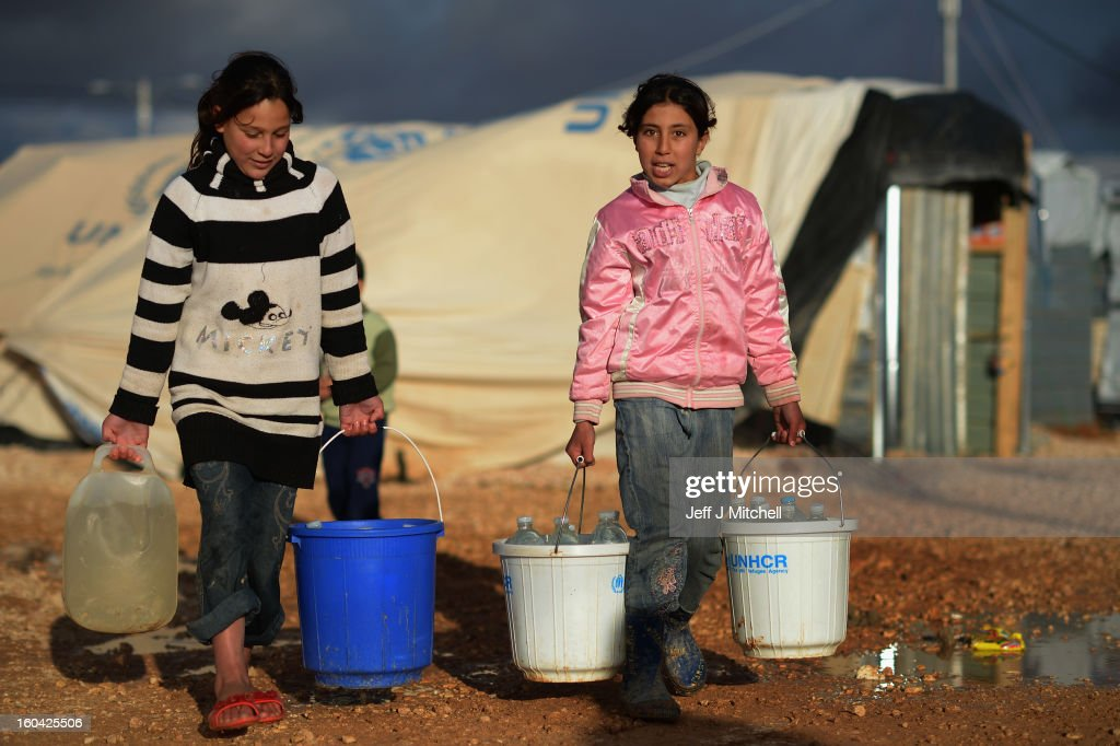 ZA'ATARI JORDAN JANUARY 31 Syrian fetch water in the Za'atari refugee camp on January 31 2013 in Za'atari Jordan Record numbers of refugees are...