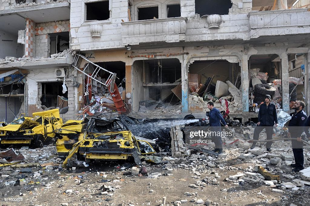 Syrian firefighters spray water on burning car at the site of a double car bomb attack in the AlZahraa neighborhood of the central Syrian city of...
