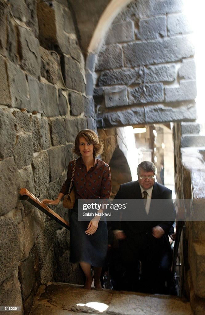 Syrian first lady Asmaa Al Assad (2nd-R) walks through the castle of Bosra March 31, 2004 at the ancient ruins of Bosra, an old Roman city in the south of Syria. Al Assad is promoting the United Nations Developing Program (UNDP) which is a program dedicated to distributing information technology (IT) throughout the local rural areas of Syria.