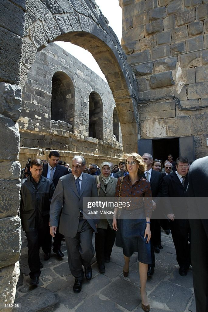 Syrian first lady Asmaa Al Assad (2nd-R) walks through the castle of Bosra March 31, 2004 at the ancient ruins of Bosra, an ancient Roman city in the south of Syria. Al Assad is promoting the United Nations Developing Program (UNDP) which is a program dedicated to distributing information technology (IT) throughout the local rural areas of Syria.