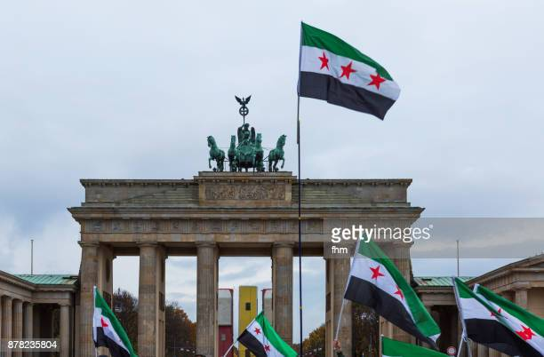 Syrian flag with Brandenburg Gate and three public transport buses standing on end - art installation called 'Monument' in front of the Brandenburg Gate in Berlin, Germany