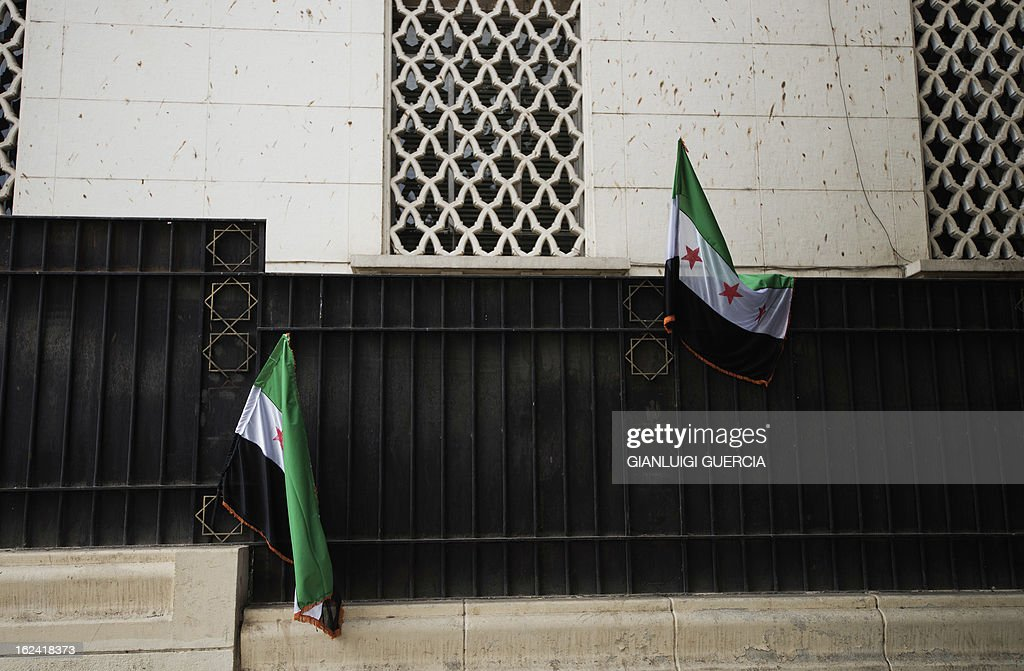 Syrian flags, currently being used by the Syrian rebels, are hung on the fence outside the Arab League headquarters in Cairo as Syrian opposition demonstrators stage a sit-in protest on February 23, 2013. The opposition National Coalition said on February 22, it will form a government to run 'liberated areas' of Syria, as monitors said more than 12 people were killed when buildings collapsed in a missile strike on the northern city of Aleppo. AFP PHOTO/GIANLUIGI GUERCIA