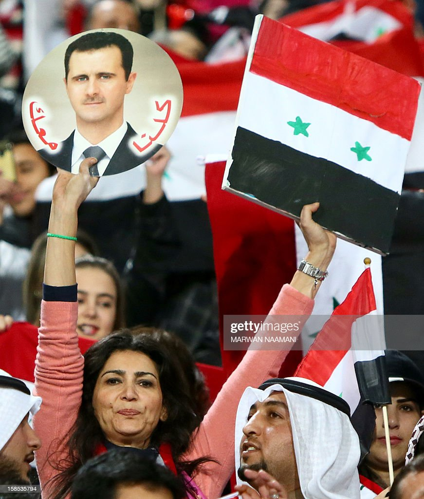 A Syrian football fan and supporter of President Bashar al-Assad waves her national flag and a picture of the embattled President during Syria's semi-final football match against Bahrain in the 7th West Asia Football Federation (WAFF) championship in Kuwait City on December 18, 2012. Syria won the match in a penalty shoot-out and go on to face Iraq in the final. AFP PHOTO/MARWAN NAAMANI
