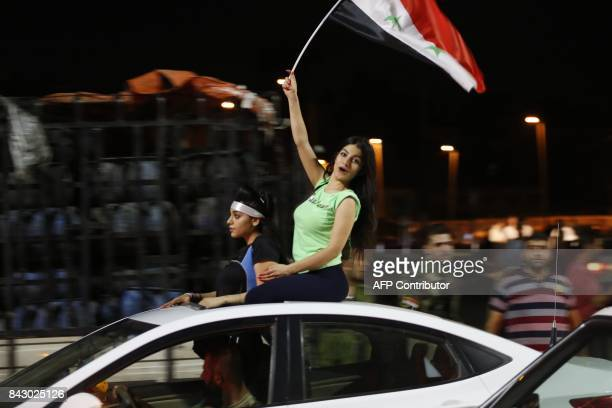 TOPSHOT Syrian football fans celebrate in the streets of Damascus after the FIFA World Cup 2018 qualification football match between Iran and Syria...