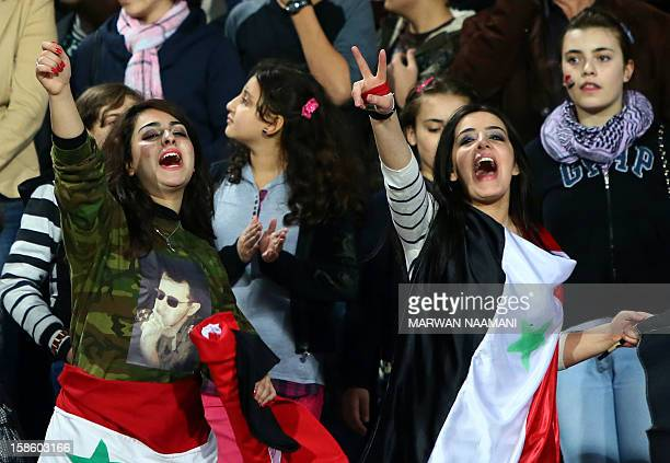 Syrian football fans one of them wearing a shirt with the picture of President Bashar alAssad reacts during Syria's final football match against Iraq...
