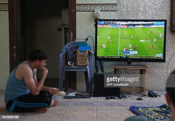 TOPSHOT Syrian football fans watch the FIFA World Cup 2018 qualification football match between Iran and Syria on television at a house in the...