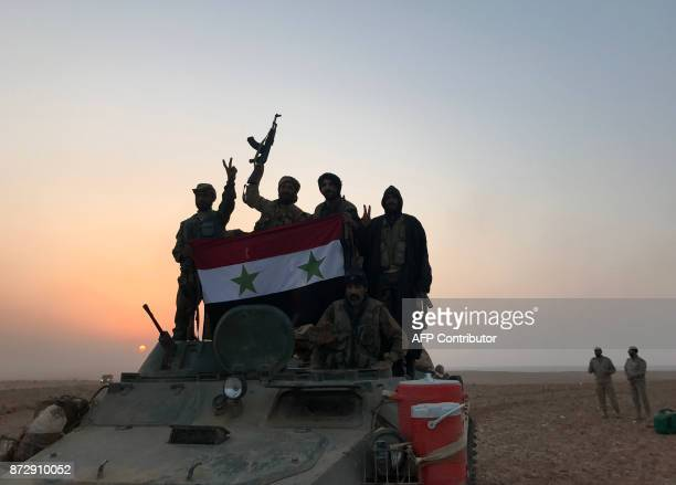 Syrian forces gestures as they carry the national flag in the village of Suway'iah near the Syrian border town of Albu Kamal on November 9 2017 / AFP...