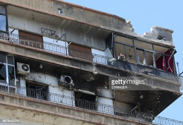 Syrian forces member is seen standing on a balcony in the government held part of the Jobar neighbourhood east of the capital Damascus on March 25...
