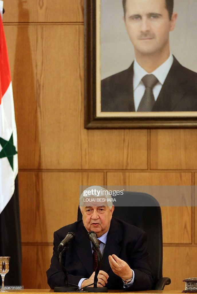 Syrian Foreign Minister Walid al-Muallem talks to media during a news conference in Damascus on February 6, 2016. Muallem warned that Syria's forces would resist any foreign ground intervention after reports that Saudi Arabia and Turkey, which both support rebel forces, could send in troops. The portrait shows Syrian President Bashar al-Assad. / AFP / LOUAI BESHARA