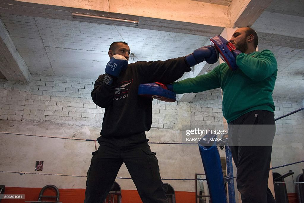 Syrian former national boxing champion, Shaaban Kattan (L) fights with his colleague Ahmad Mashallah at the Shahba boxing club that they opened in Syria's war-torn Aleppo city on February 10, 2016 in a rebel held district of the city. Kattan and Mashallah opened the club in the summer of 2015 to bring boxing back to a conflict-ravaged city. Bathed in the fluorescent light of a sparse basement in Aleppo, young boys pummel red punching bags under the close supervision of a former national boxing champion MASRI