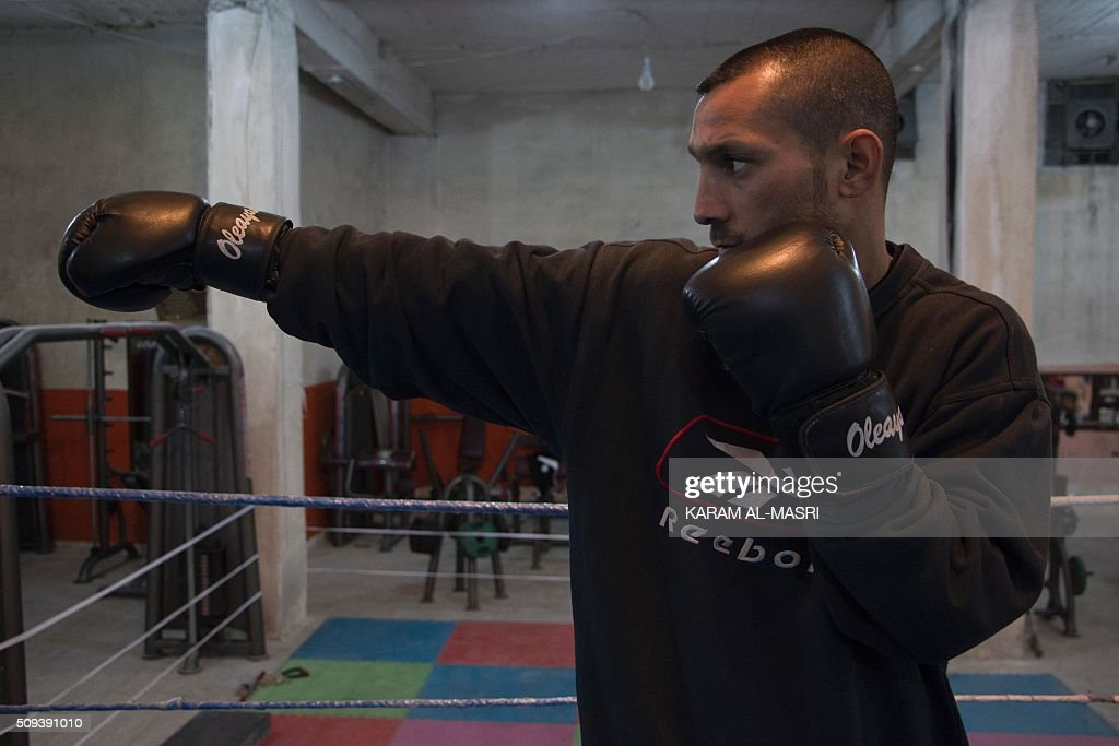 Syrian former national boxing champion, Shaaban Kattan leads a training session at the Shahba boxing club that he founded in Syria's war-torn Aleppo city on February 10, 2016 in a rebel held district of the city. Along with colleague Ahmad Mashallah, Kattan opened the club in the summer of 2015 to bring boxing back to a conflict-ravaged city. Bathed in the fluorescent light of a sparse basement in Aleppo, young boys pummel red punching bags under the close supervision of a former national boxing champion MASRI