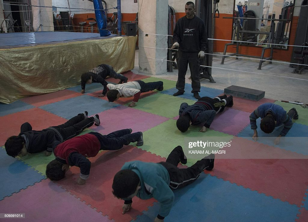 Syrian former national boxing champion, Shaaban Kattan (C) leads a training session at the Shahba boxing club that he founded in Syria's war-torn Aleppo city on February 10, 2016 in a rebel held district of the city. Along with colleague Ahmad Mashallah, Kattan opened the club in the summer of 2015 to bring boxing back to a conflict-ravaged city. Bathed in the fluorescent light of a sparse basement in Aleppo, young boys pummel red punching bags under the close supervision of a former national boxing champion MASRI