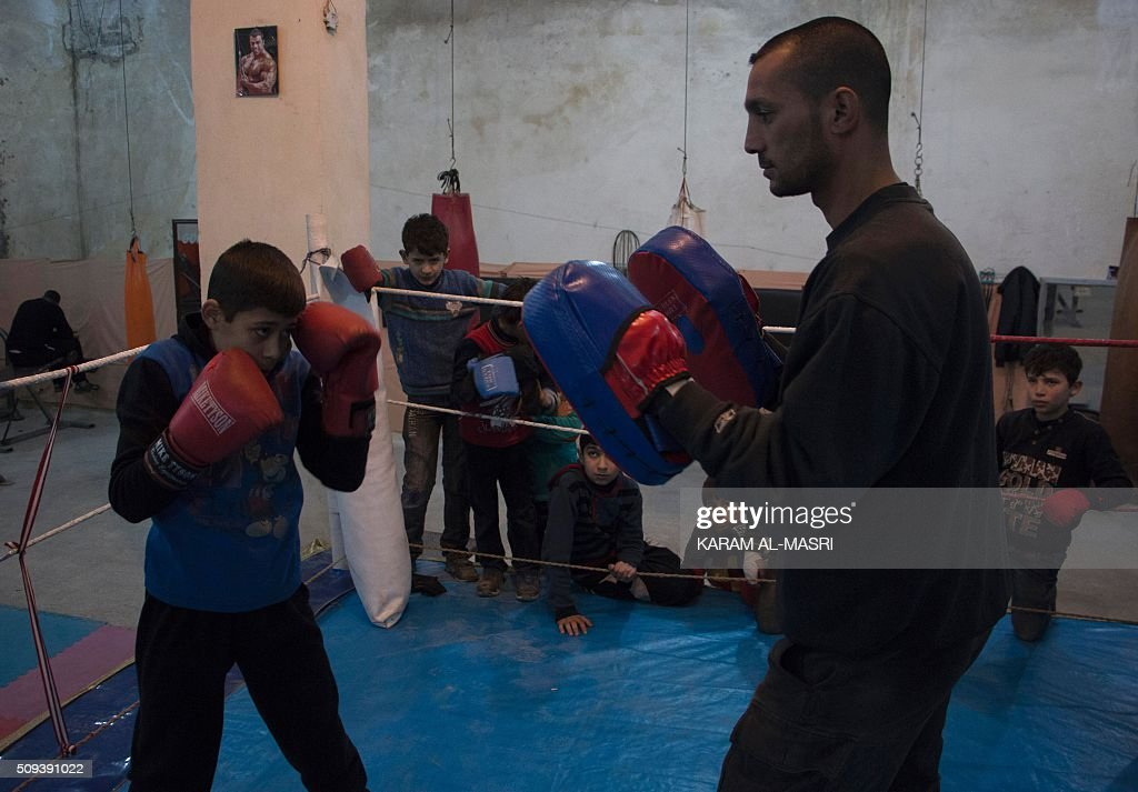 Syrian former national boxing champion, Shaaban Kattan (R) leads a training session at the Shahba boxing club that he founded in Syria's war-torn Aleppo city on February 10, 2016 in a rebel held district of the city. Along with colleague Ahmad Mashallah, Kattan opened the club in the summer of 2015 to bring boxing back to a conflict-ravaged city. Bathed in the fluorescent light of a sparse basement in Aleppo, young boys pummel red punching bags under the close supervision of a former national boxing champion MASRI
