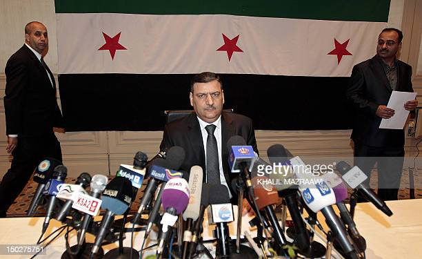 Syrian former prime minister Riad Hijab who defected last week prepares to hold a press conference in the Jordanian capital Amman while sitting in...