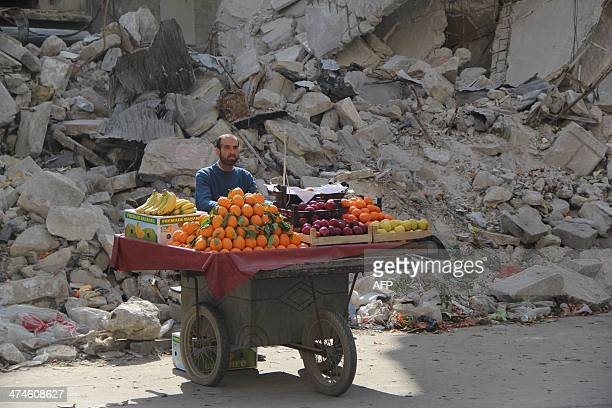 A Syrian fruit vendor waits for customers next to a damaged building on February 24 2014 in the Shaar neighborhood of the northern city of Aleppo...