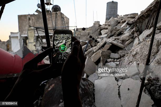 A Syrian gamer uses the Pokemon Go application on his mobile to catch a Pokemon amidst the rubble in the besieged rebelcontrolled town of Douma a...