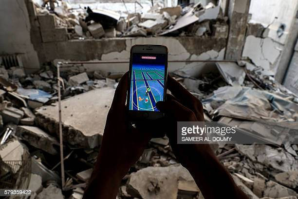 A Syrian gamer uses the Pokemon Go application on his mobile to search for Pokemons amidst the rubble in the besieged rebelcontrolled town of Douma a...
