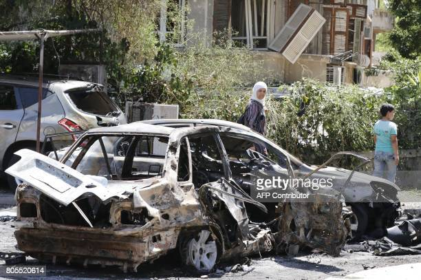 A Syrian girl and a child walk past a charred vehicle at the site of a suicide bomb attack in the capital Damascus' eastern Tahrir Square district on...