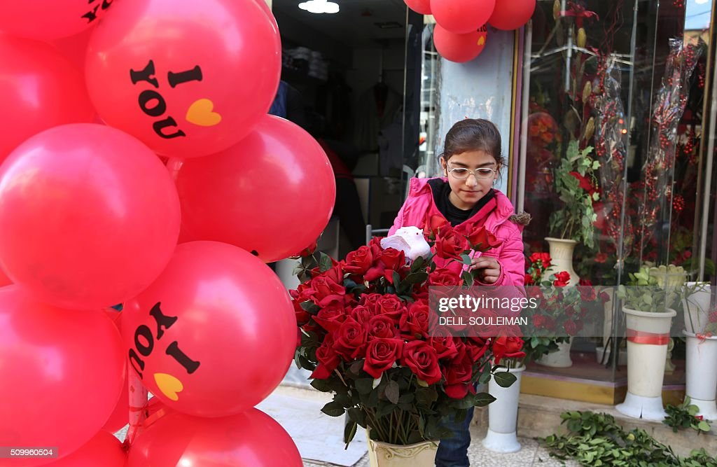 A Syrian girl arranges flowers at a shop displaying Valentine's day gifts in the northeastern city of Qamishli on February 13, 2016. / AFP / DELIL SOULEIMAN