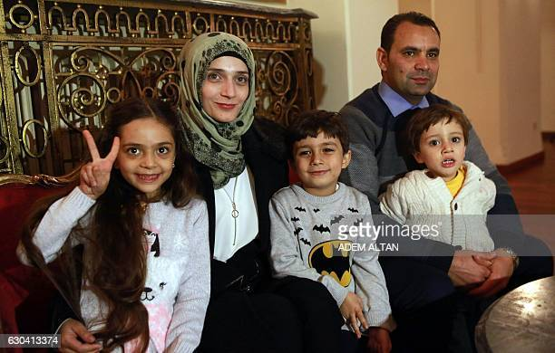 Syrian girl Bana alAbed known as Aleppo's tweeting girl gestures as she poses with her family her mother Fatemah her father Ghassan and her brothers...