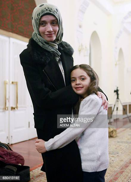 Syrian girl Bana alAbed known as Aleppo's tweeting girl hugs her mother Fatemah during an interview in Ankara Turkey on December 22 2016 The young...