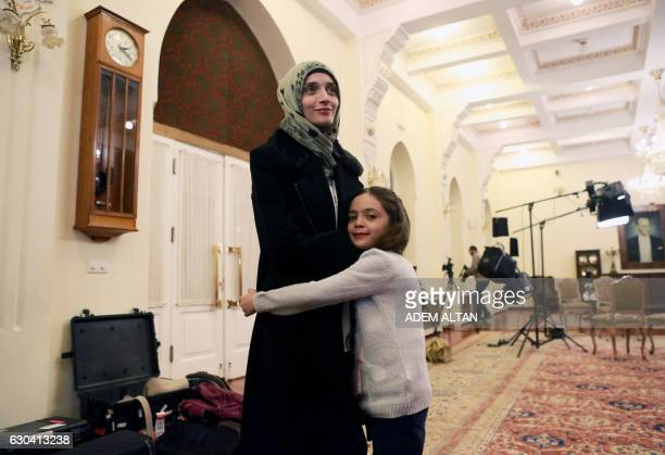 TOPSHOT Syrian girl Bana alAbed known as Aleppo's tweeting girl hugs her mother Fatemah during an interview in Ankara Turkey on December 22 2016 The...