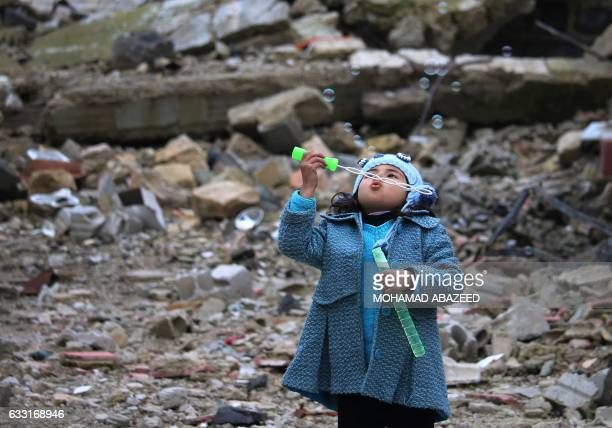 A Syrian girl blows bubbles amid the rubble of destroyed buildings in the rebelheld area of Daraa in southern Syria on January 31 2017 / AFP /...