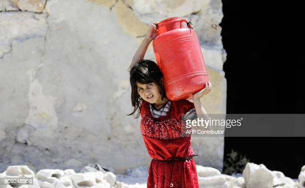 A Syrian girl carries a large jug of water on her back while on her way home in the Kallaseh district of the northern city of Aleppo on July 5 2017...