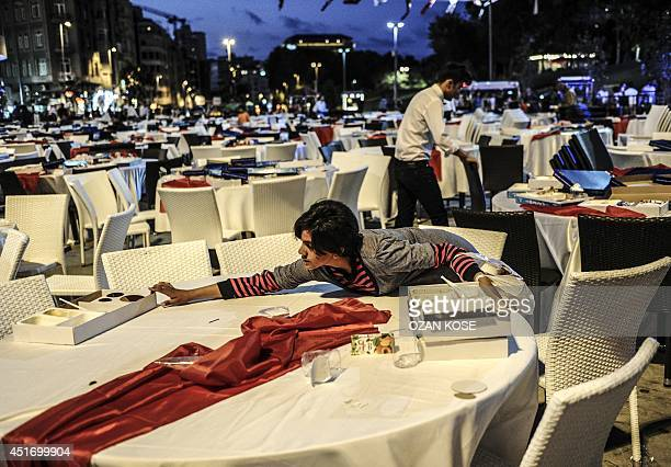 A Syrian girl collects leftovers from tables after Turkish people break their fasting on July 4 at Taksim square during the holy month of Ramadan in...