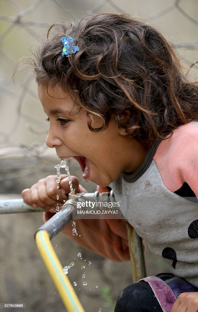 A Syrian girl drinks from a water pipe a Syrian refugee camp, in the southern Lebanese town of Zahrani on May 3, 2016. / AFP / MAHMOUD